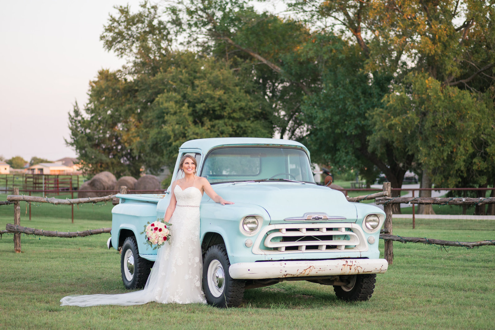 Bride poses with vintage blue truck at lone oak barn wedding venue in Round Rock Texas