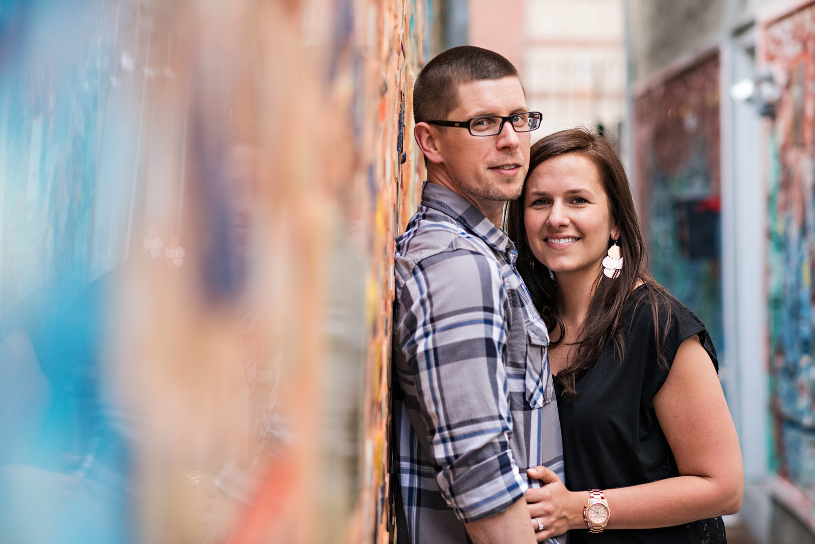 A happy couple lean against a south street wall covered in glass and shiny objects.