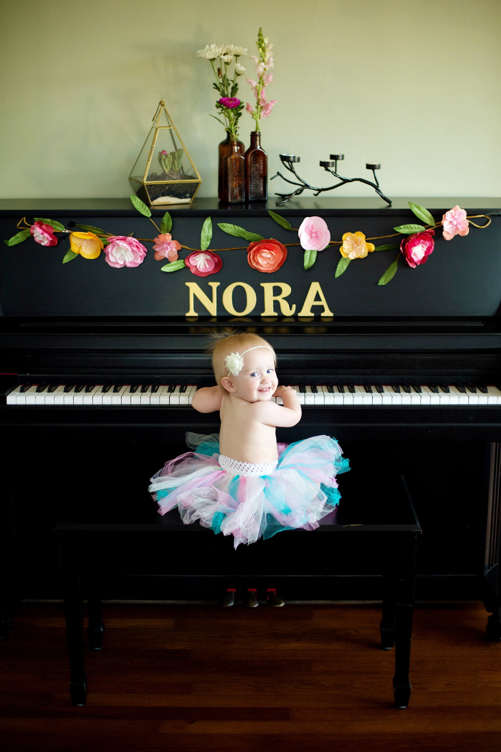 an infant baby in a tutu sits at a piano and looks over her shoulder
