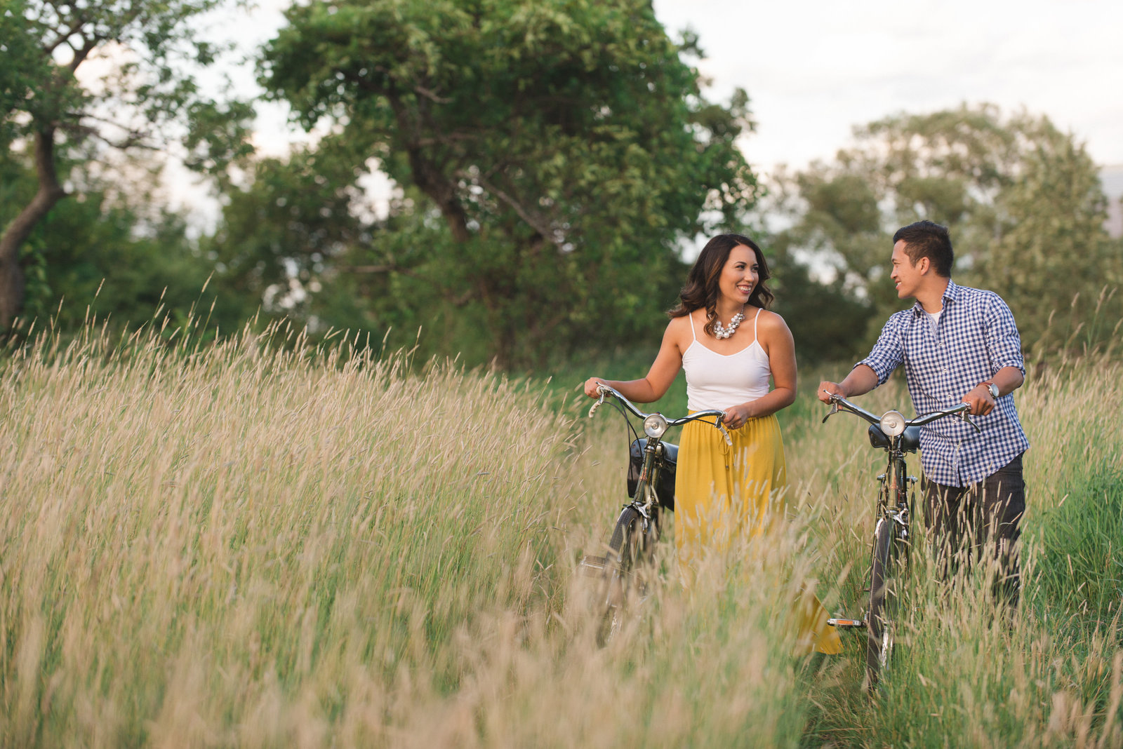 couple walking in the tall grass with raleigh vintage bicycles