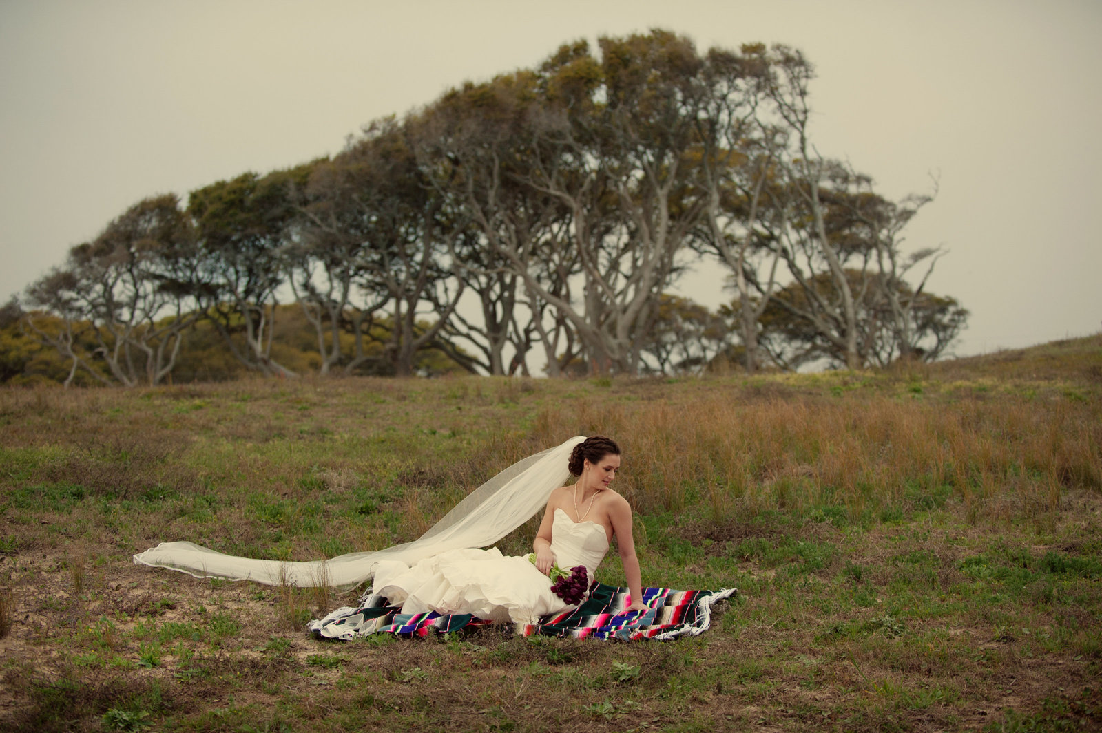 bride sits in grass at fort fisher