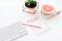 keyboard on desk with fruit and notepad