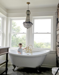 Photo of French chandelier and clawfoot bathtub in a bathroom remodel.