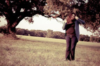 San Antonio Photographer Irene Castillo dancing under a tree in a field