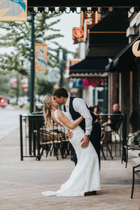 A bride and groom pause for a kiss under the Blackhawk hotel awning on Main street in Cedar Falls, IA