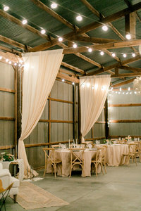wedding reception decorated with white curtains and lights