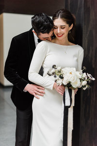 Bride and groom at downtown wedding venue, black velvet tuxedo