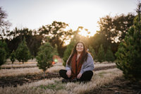 San Antonio Photographer Irene Castillo sitting a field of trees