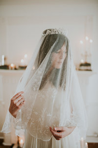 Beautiful bride wearing a vintage veil surrounded by candles