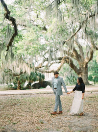 husband and wife walking under spanish moss