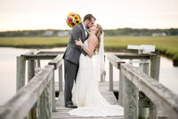 Bride and groom kiss on dock over water