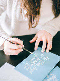 Artist addressing envelopes with calligraphy