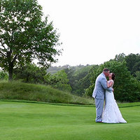 Happy couple kissing on a golf course while having a video filmed