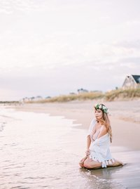 photo of woman on the beach at sunrise in a white shawl, lingerie, and flower crown