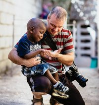 professional wedding photographer, christopher tyson holding child in haiti