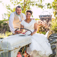 Photo of newlywed Couple sitting on farm tractor by Miami Wedding Photographer from White House Wedding Photography