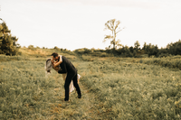 man dipping woman while standing in field