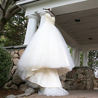 beautiful wedding dress on display hanging on a wraparound porch