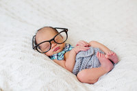 Newborn photo with bowtie and hipster glasses.