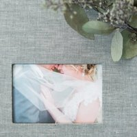 Custom linen fabric fine art photo album with image cutout, displayed with eucalyptus