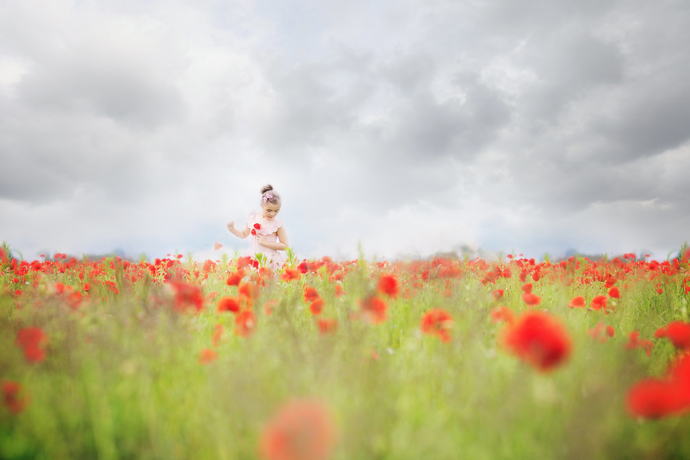 girl running through poppy firld