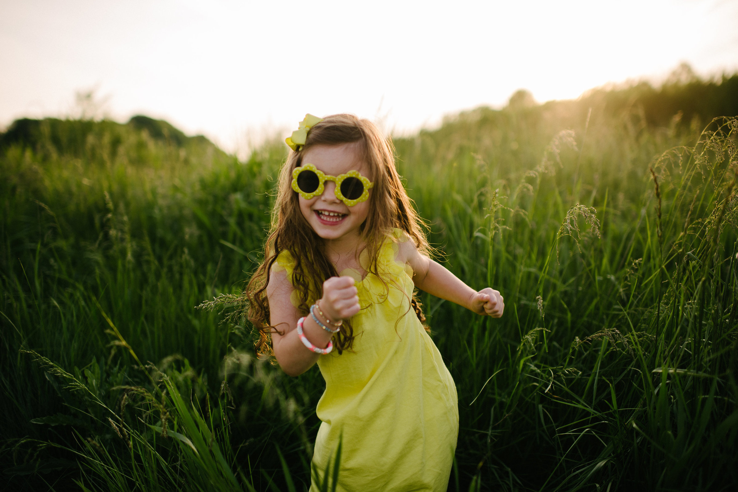 little girl wearing yellow sundress and sunglasses dancing in field