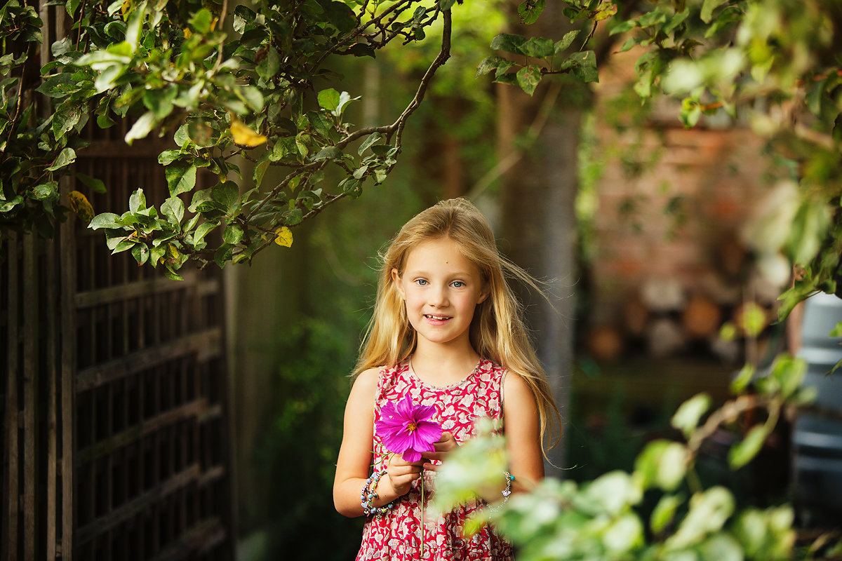 little girl holding a flower in the garden