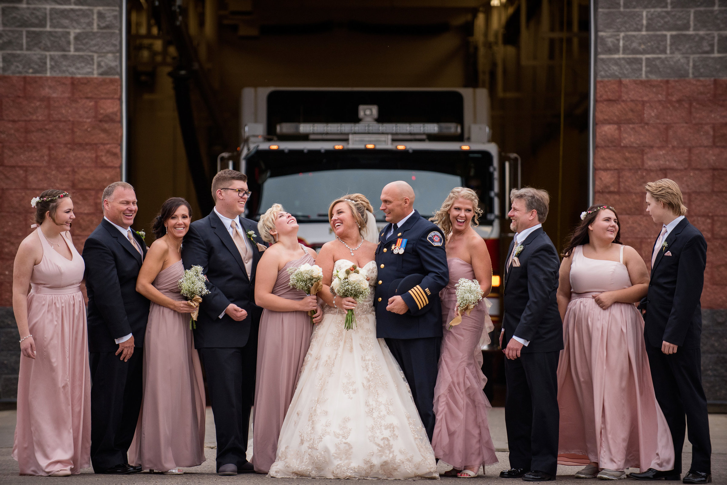 Fire Fighter and wedding party at a firehall in Fort McMurray Alberta by Chrystal Stringer