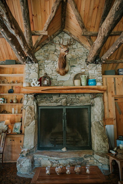 rustic wedding reception, cabin at on the windfall, rustic reception, on the windfall wedding photographer, salty spruce studio, deer head above fireplace, inside rustic cabin on pond, nc wedding photographers, on the windfall north carolina wedding photographer