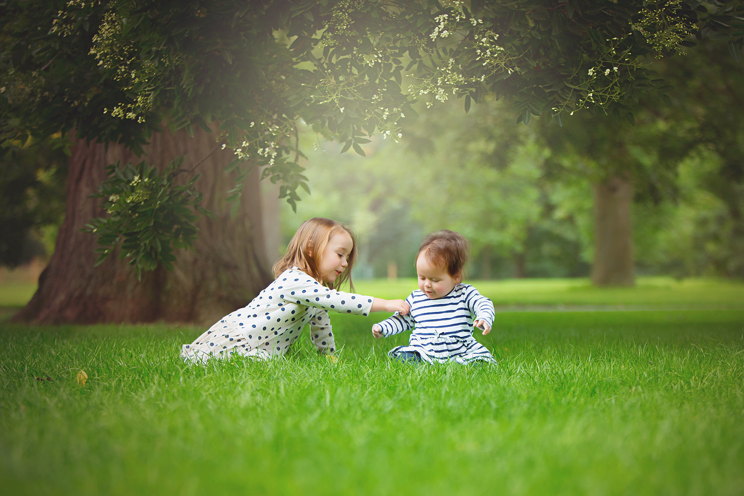 sisters playing on the grass under a tree