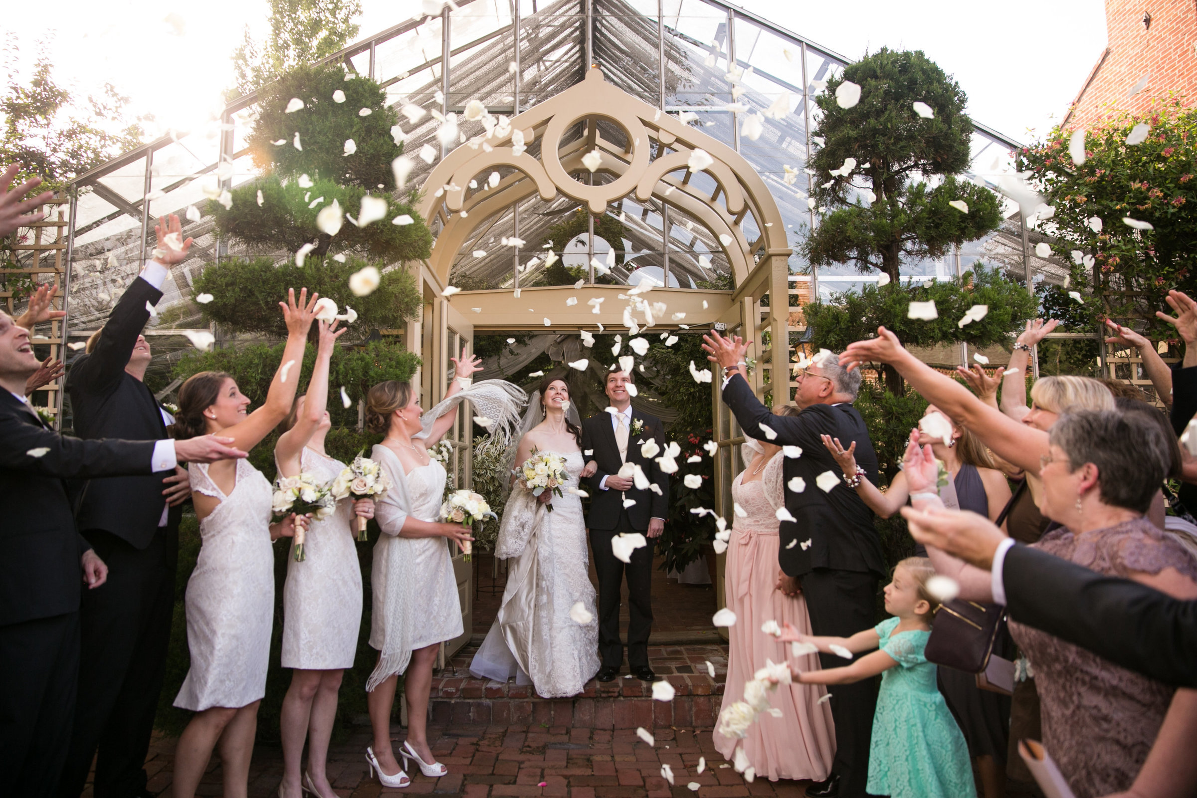 Bride and Groom Exit St. Charles Conservatory Wedding with guest throwing flower petals