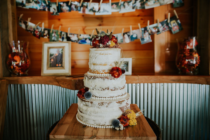 naked cake with dried flowers, naked cake, boone nc wedding cakes, on the windfall weddings, on the windfall lansing nc, on the windfall elopement photographers, rustic wedding, cake in cabin, salty spruce studio, fall wedding inspo, on the windfall north carolina wedding photographer