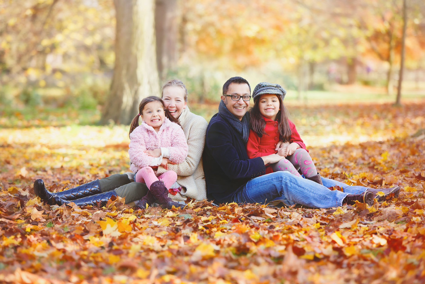 family portrait sitting in autumn leaves