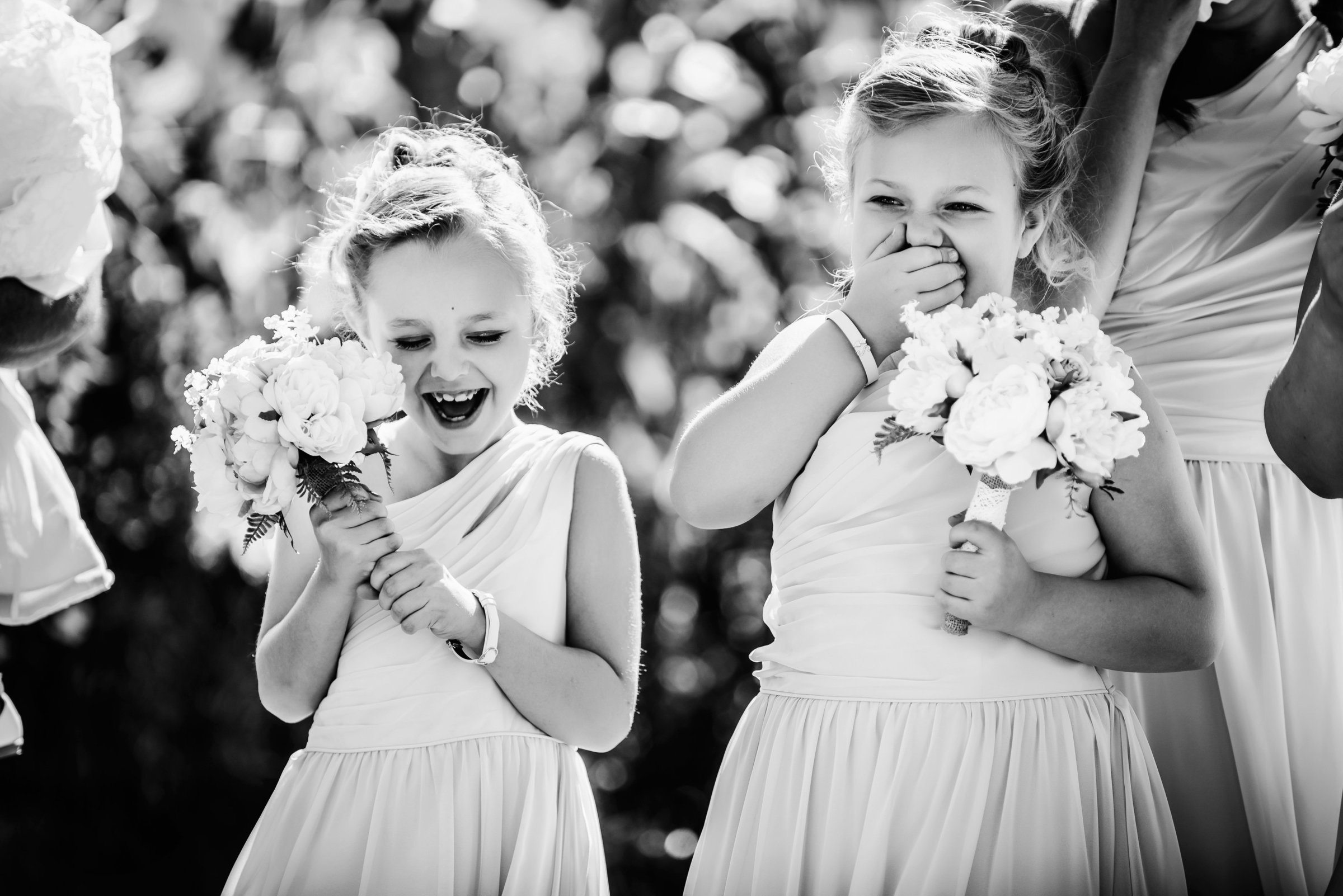 Flower girls laughing during wedding ceremony at Dunvegan Garden in Fort McMurray Alberta