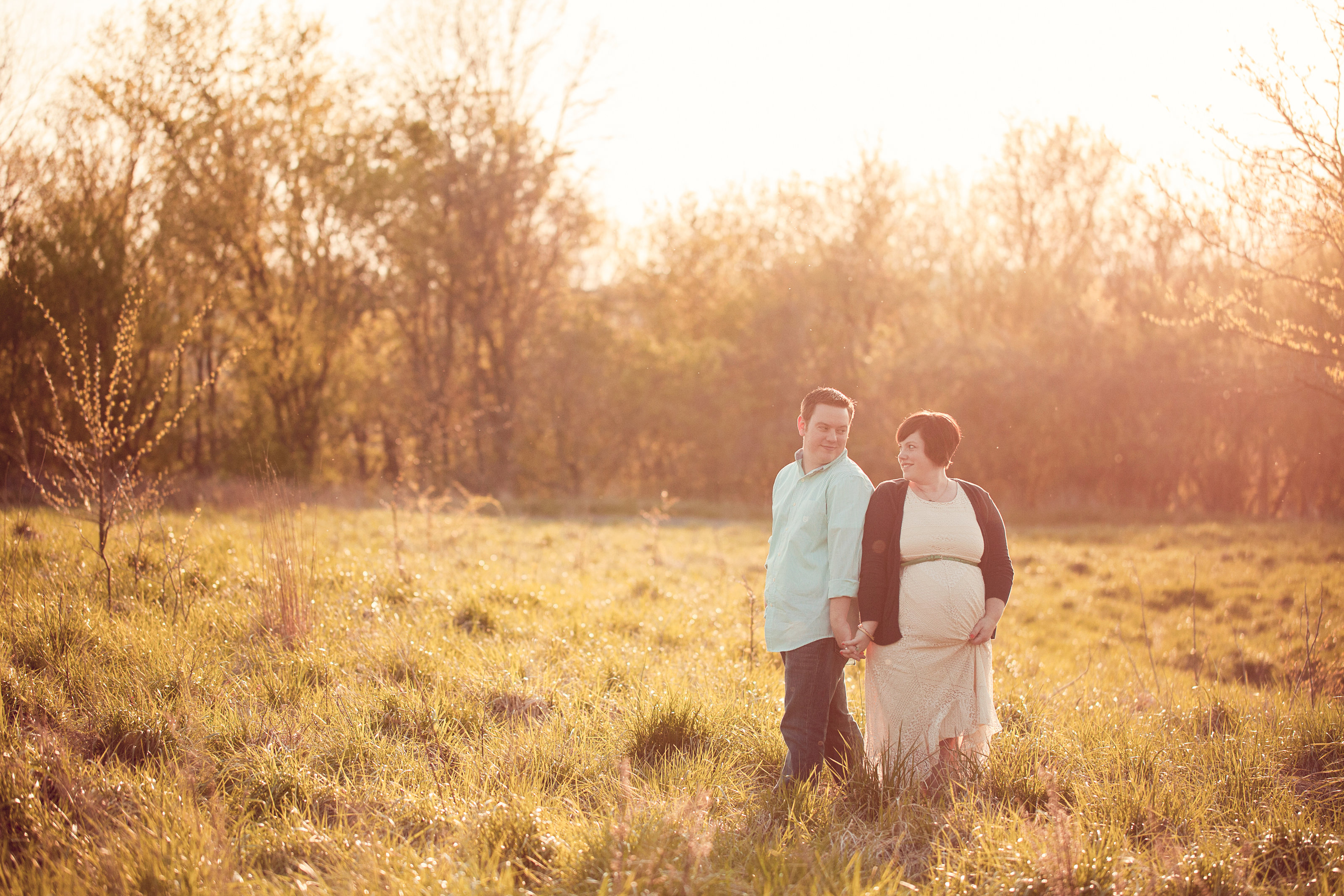 PA baby bump mom and dad stand in long grass photo at sunset