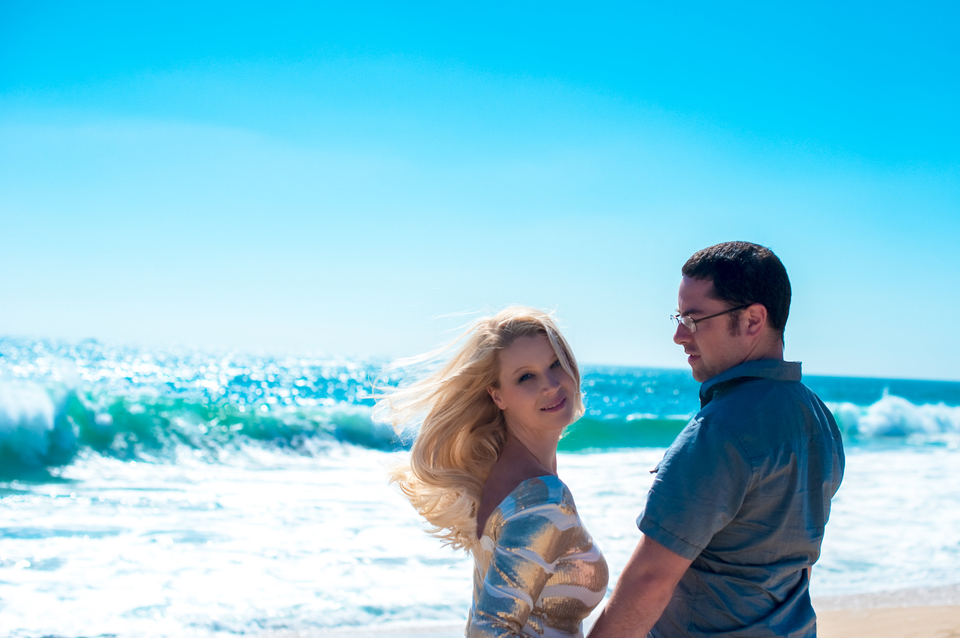 San Diego couple on the beach with wind blowing