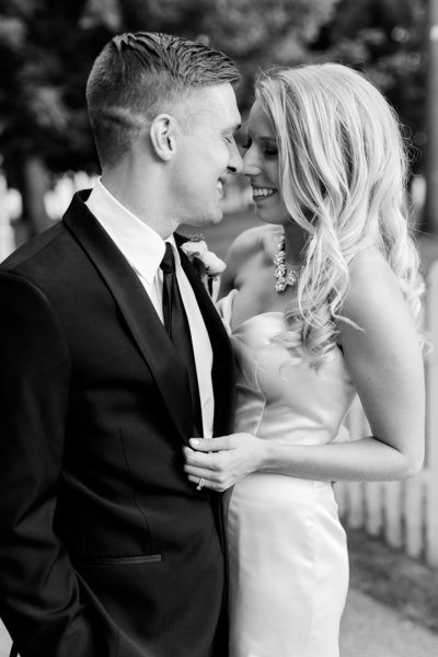 Bride and groom embrace in laughing pose