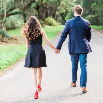 Engaged couple walks down road to the Avenue of Oaks, Magnolia Plantation, Charleston, South Carolina