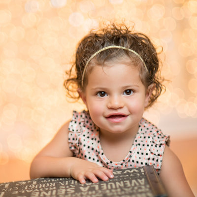 beautiful girl toddler smile gold glitter backdrop festive