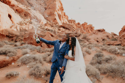 Love is love. Same sex elopement popping champagne at Redstone in Valley of Fire, Las Vegas NV