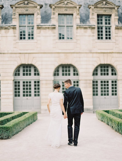 Bride and groom exchange some private words  in a French garden wedding