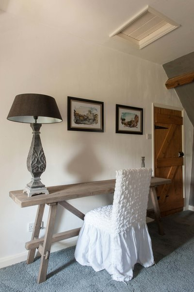 Side-table by Hoffz Interior and chair with cover by Arte Pura in one of the bedrooms in Bank Cottage in the Cotswolds. Interior design project realised by Arte di Vita Interiors.
