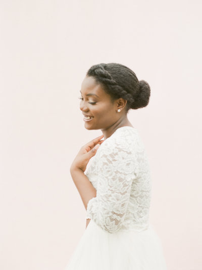 Beautiful black bride with braided hair in lace long-sleeved wedding gown in front of pale pink backdrop