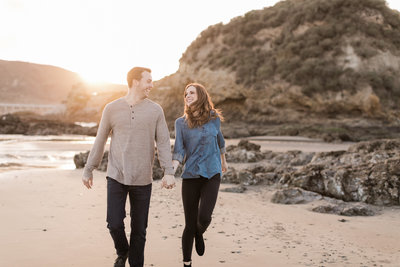 couple laughing and skipping on the beach in Avila, ca on their engagement session