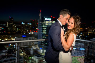 Bride and Groom with downtown lights behind them at The Ultimate Skybox