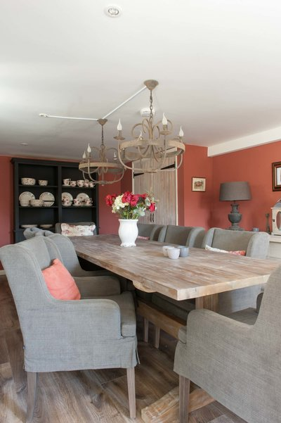 Dining table in the dining room at Bank Cottage in the Cotswolds. Interior design project by Arte di Vita Interiors. Library Red chalk paint on the wall.