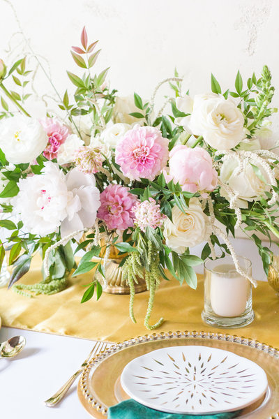 Pink and white flower centerpiece in gold vase, candles on gold tablerunner, gold charger with white and gold plate, gold flatware