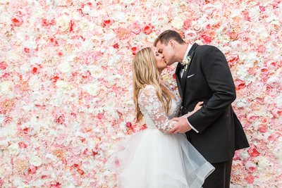 Gabby and trevors leal vineyard wedding. Photo of couple kissing in front of a blush flower wall