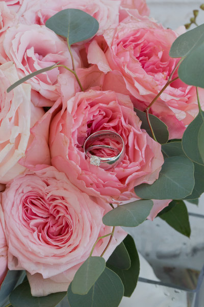 Pink peonies with eucalyptus leaves hold wedding rings
