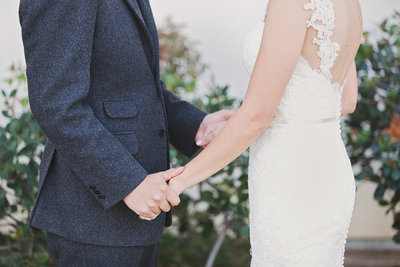 bride and groom holding hands at their wedding.